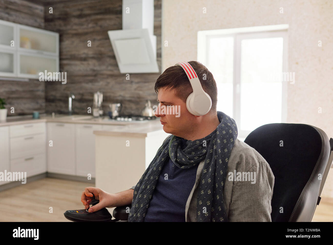 Physically impaired man listening to music with headphones at home - Stock Image