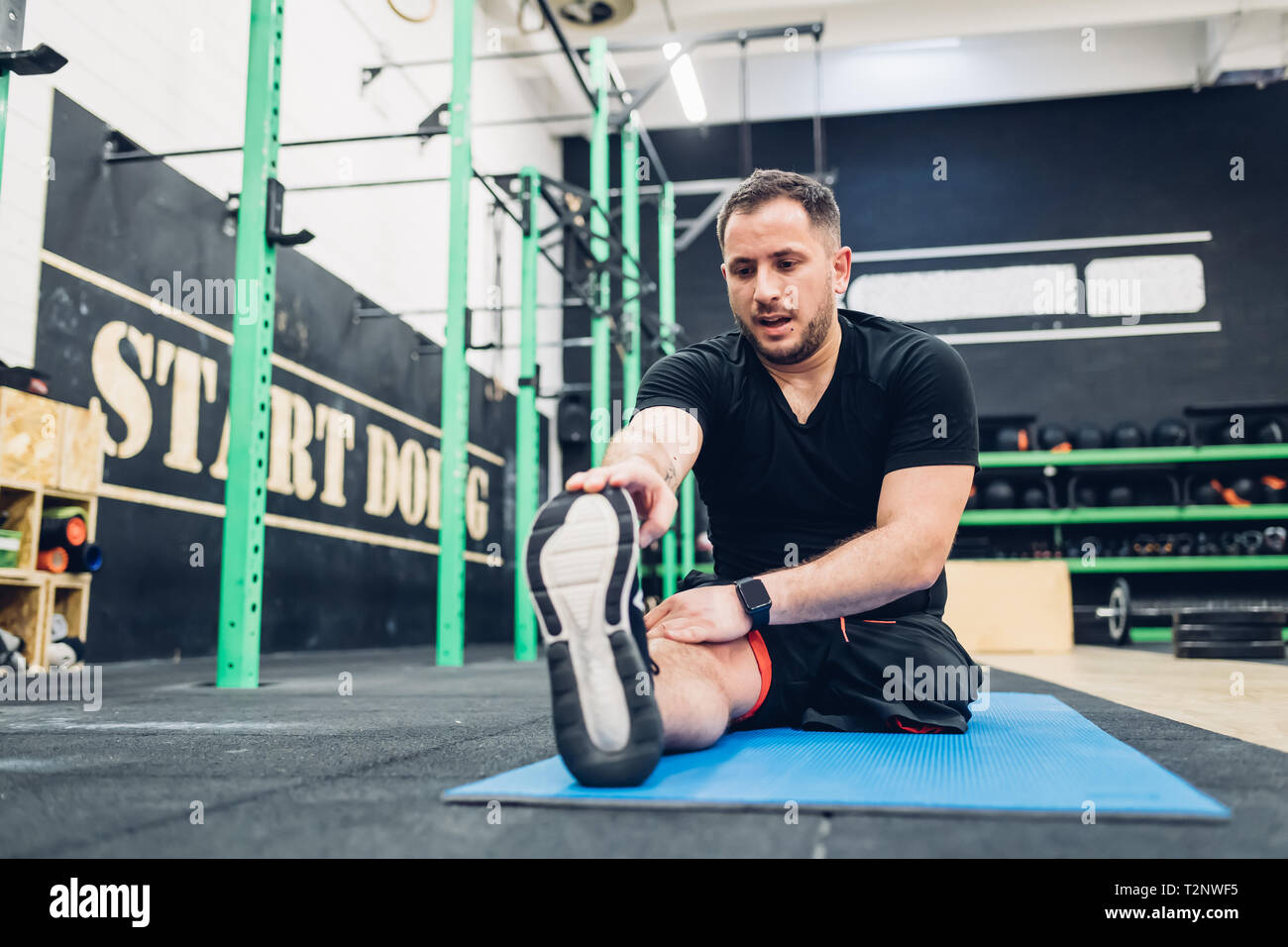 Man with disability stretching in gym - Stock Image