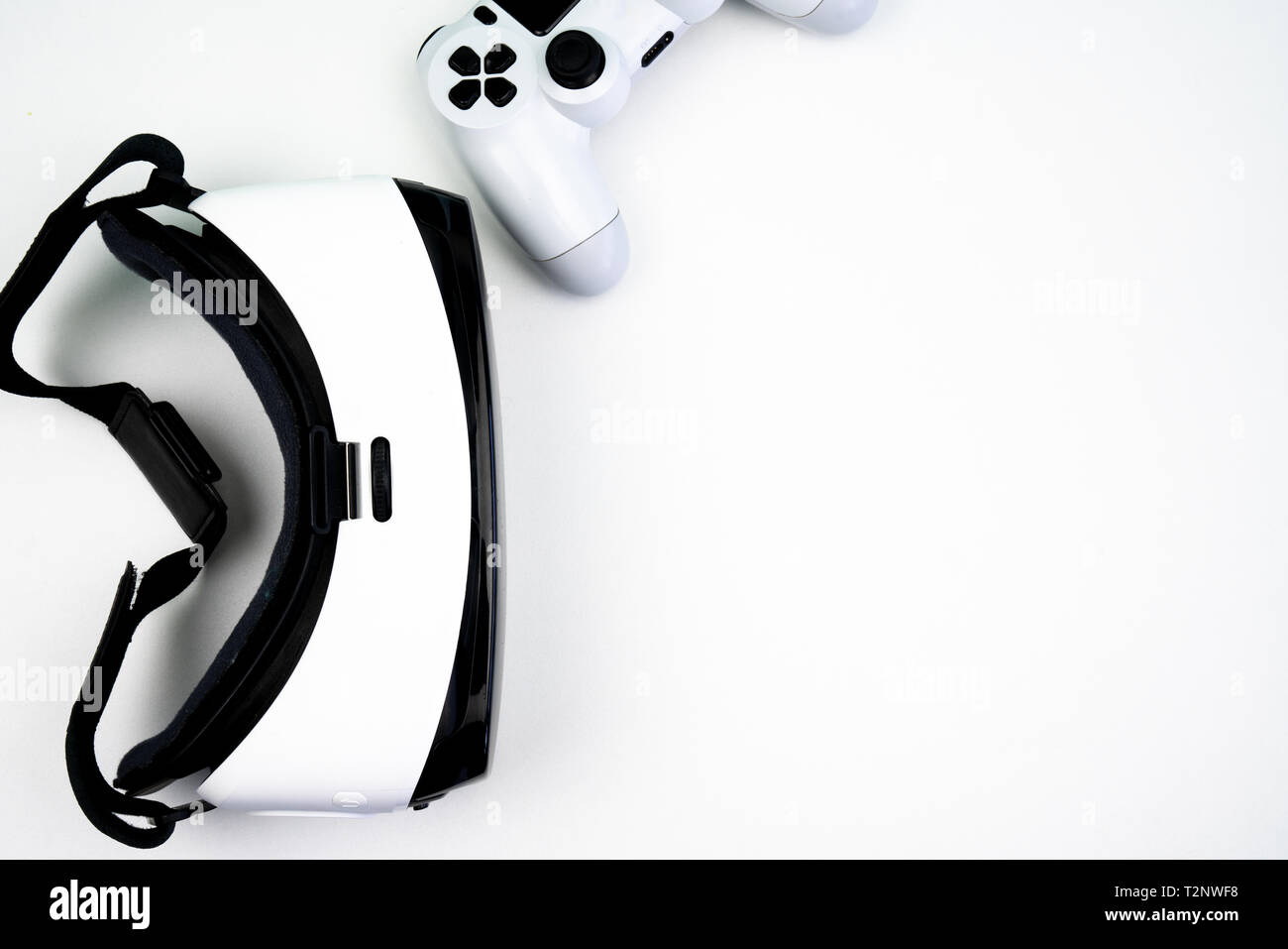Top view of a virtual reality headset with a game controller on a white background. Having fun playing with it - Stock Image