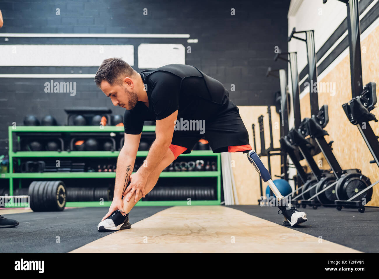 Man with prosthetic leg stretching in gym Stock Photo