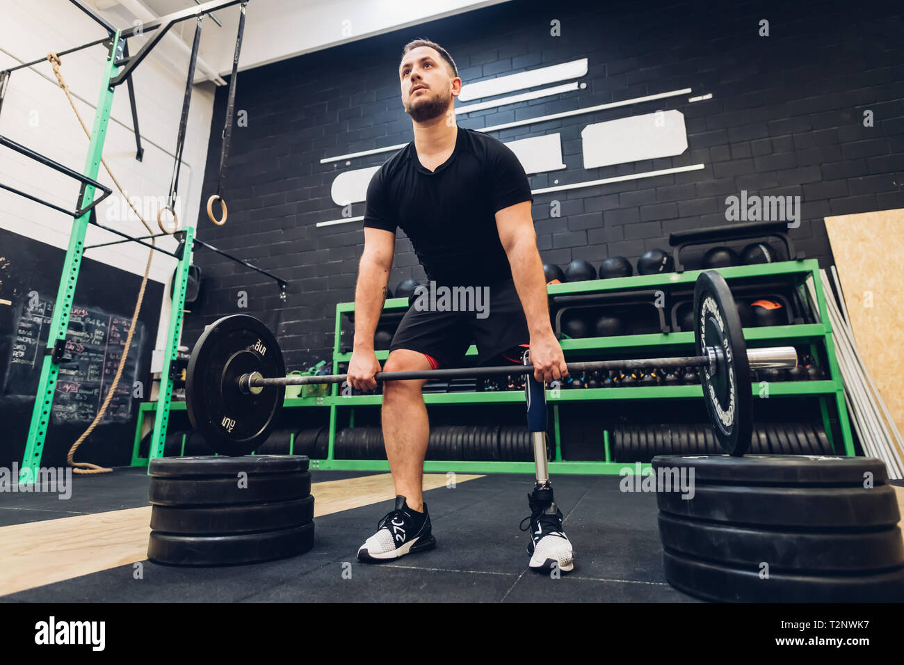 Man with prosthetic leg weight training in gym Stock Photo