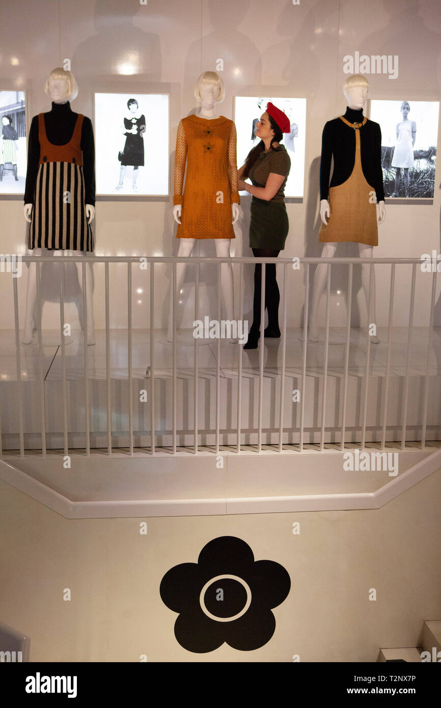 A member of staff in a Quant dress adjusts a display model at the exhibition 'Mary Quant', which opens at the Victoria and Albert Museum, London, show - Stock Image