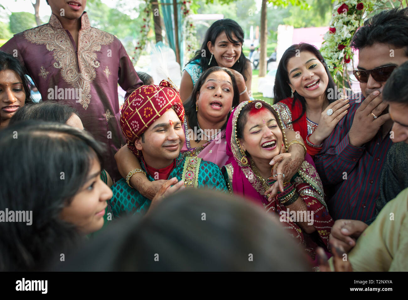 The bride and groom at an Indian wedding, surrounded by friends and family. - Stock Image