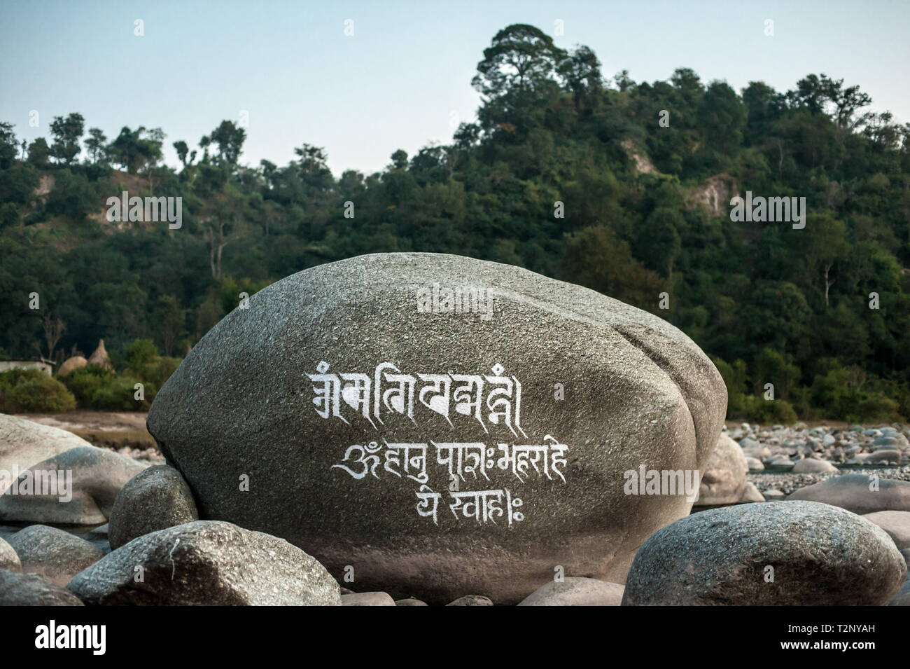 A Tibetan mantra is carved on a huge boulder in a riverbed, under Dharamshala, India: The home in exile of the Dali Lama and thousands of Tibetans. - Stock Image