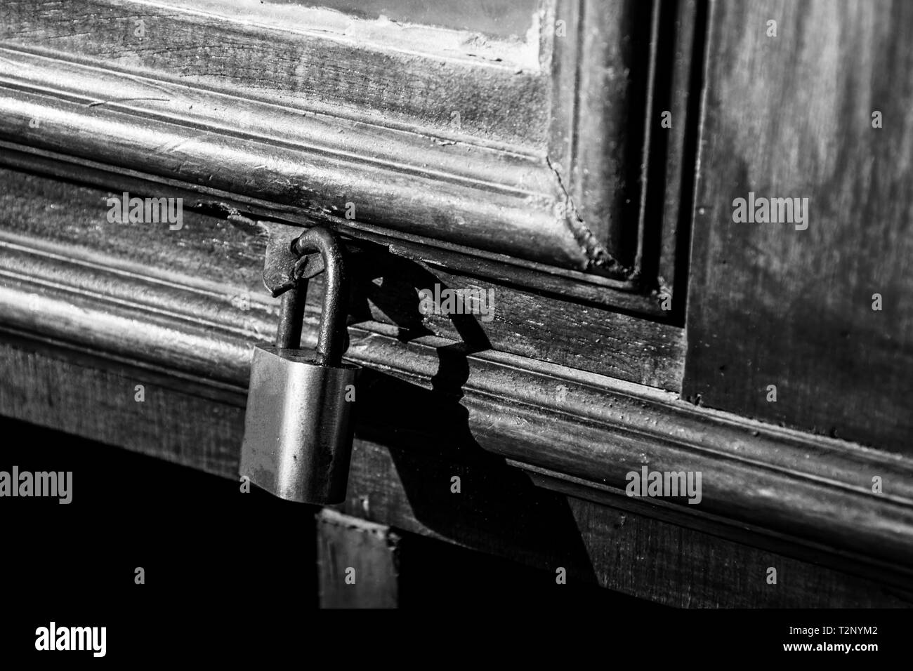 Old lock on a wooden door with rusty closed padlock, Vintage Black and white photo - Stock Image