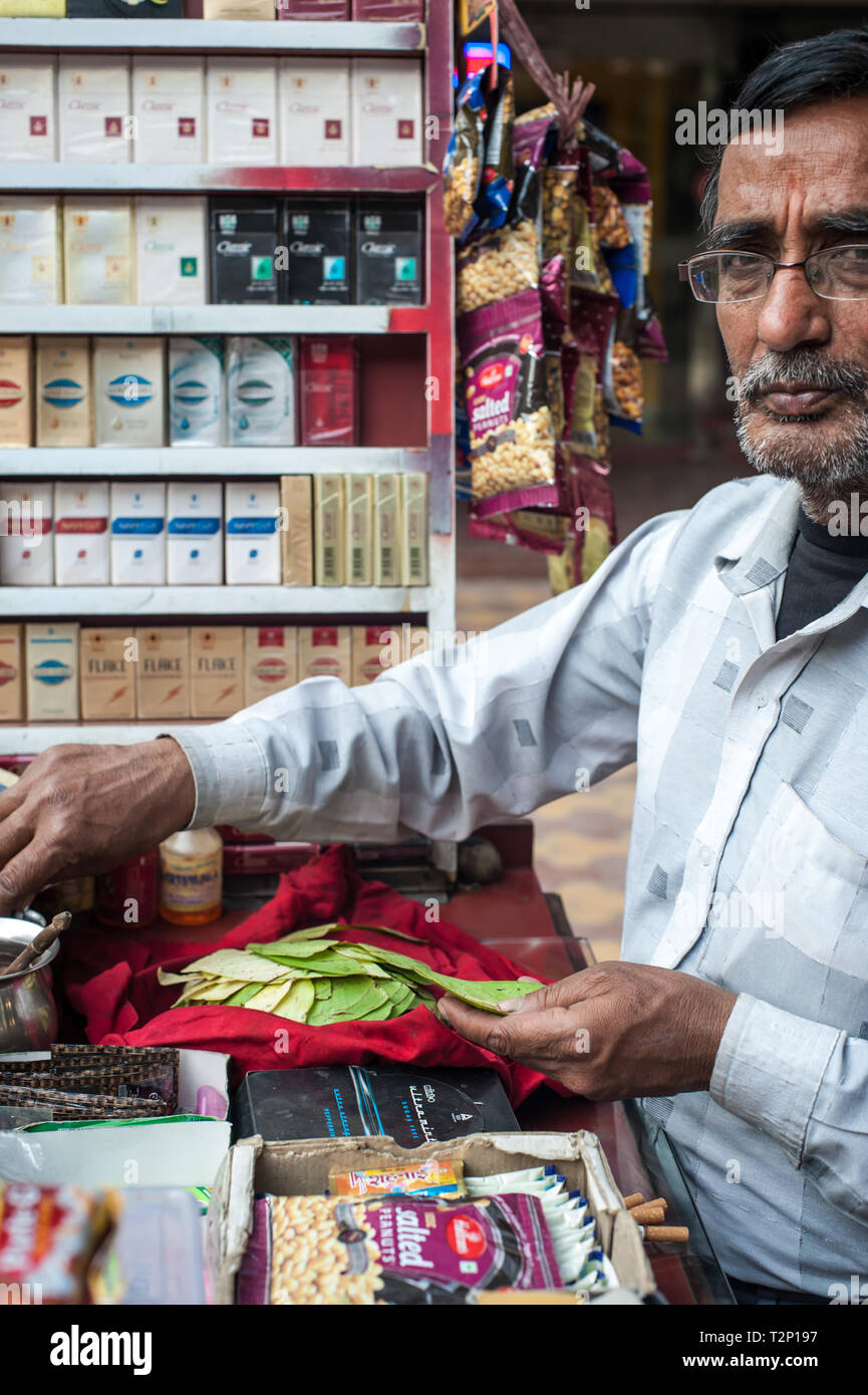 A man selling Paan in India, with his stall of cigarettes and snacks. - Stock Image