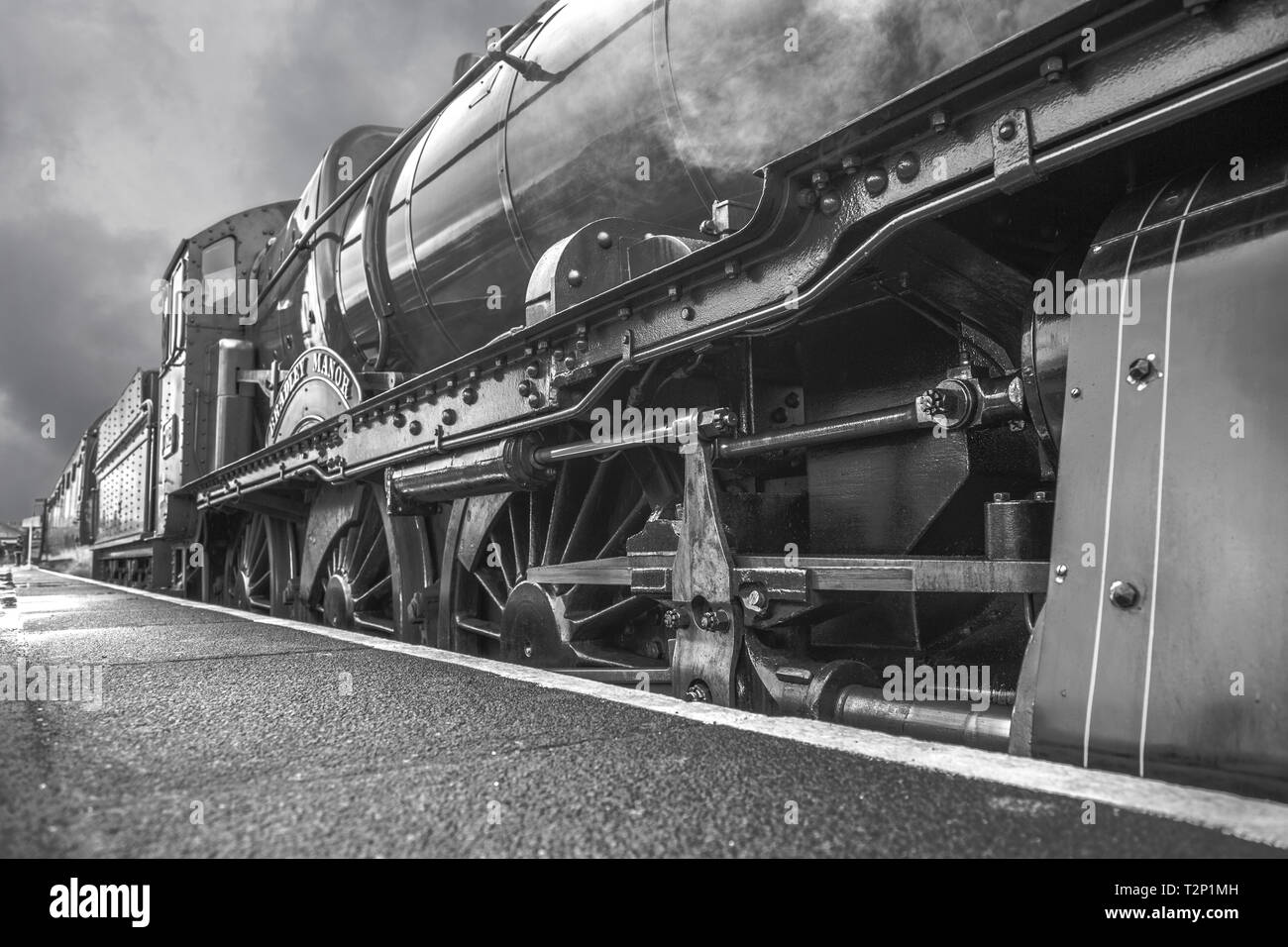 Black and white, moody, close-up side view of a vintage UK steam train awaiting departure alongside station platform, taken from a very low angle. - Stock Image