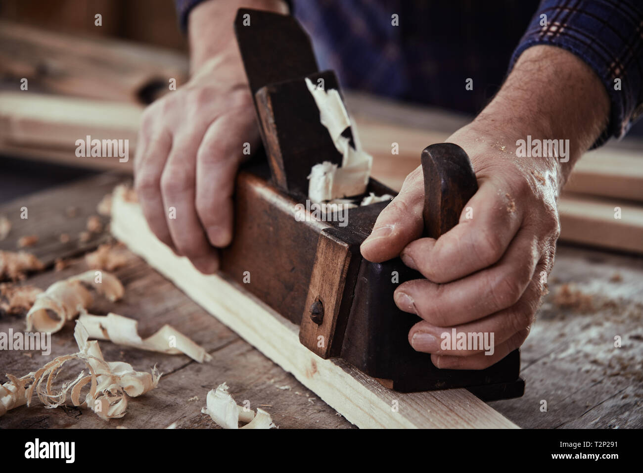 Hands of a carpenter, woodworker or joiner using a vintage plane to smooth the surface of a plank of lumber on his workbench - Stock Image