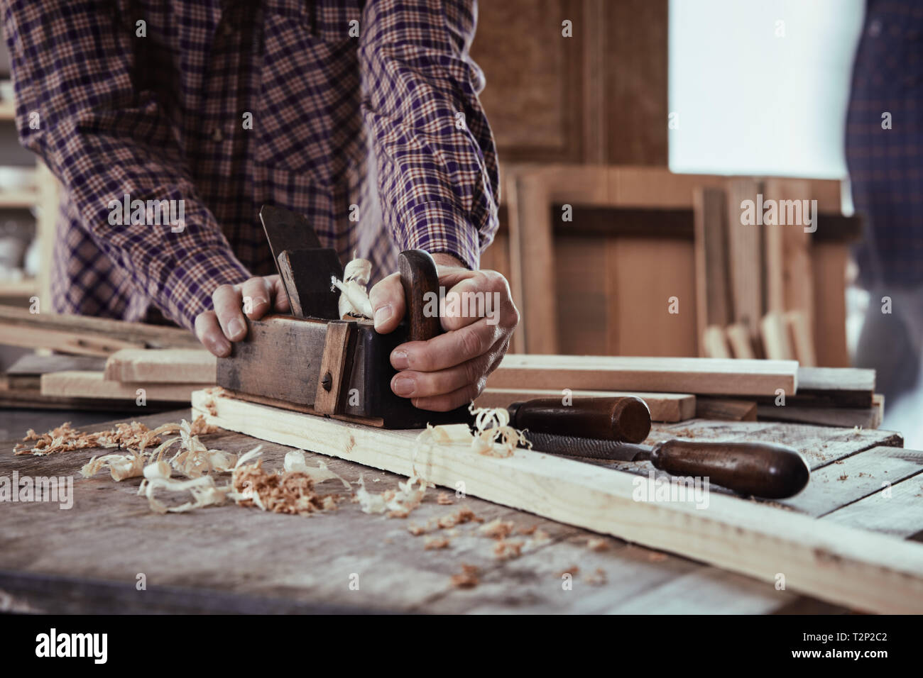 Carpenter or woodworker using an old wooden plane to smooth the surface of planks of fresh lumber in a woodworking workshop - Stock Image