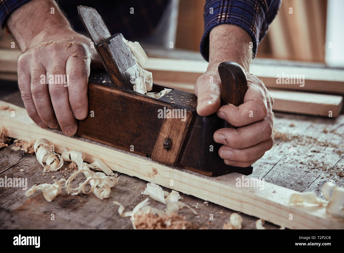 Woodworker using a plane to smooth down the surface of a plank of lumber on his workbench in a close up view on his hands with sawdust and fresh shavi - Stock Image