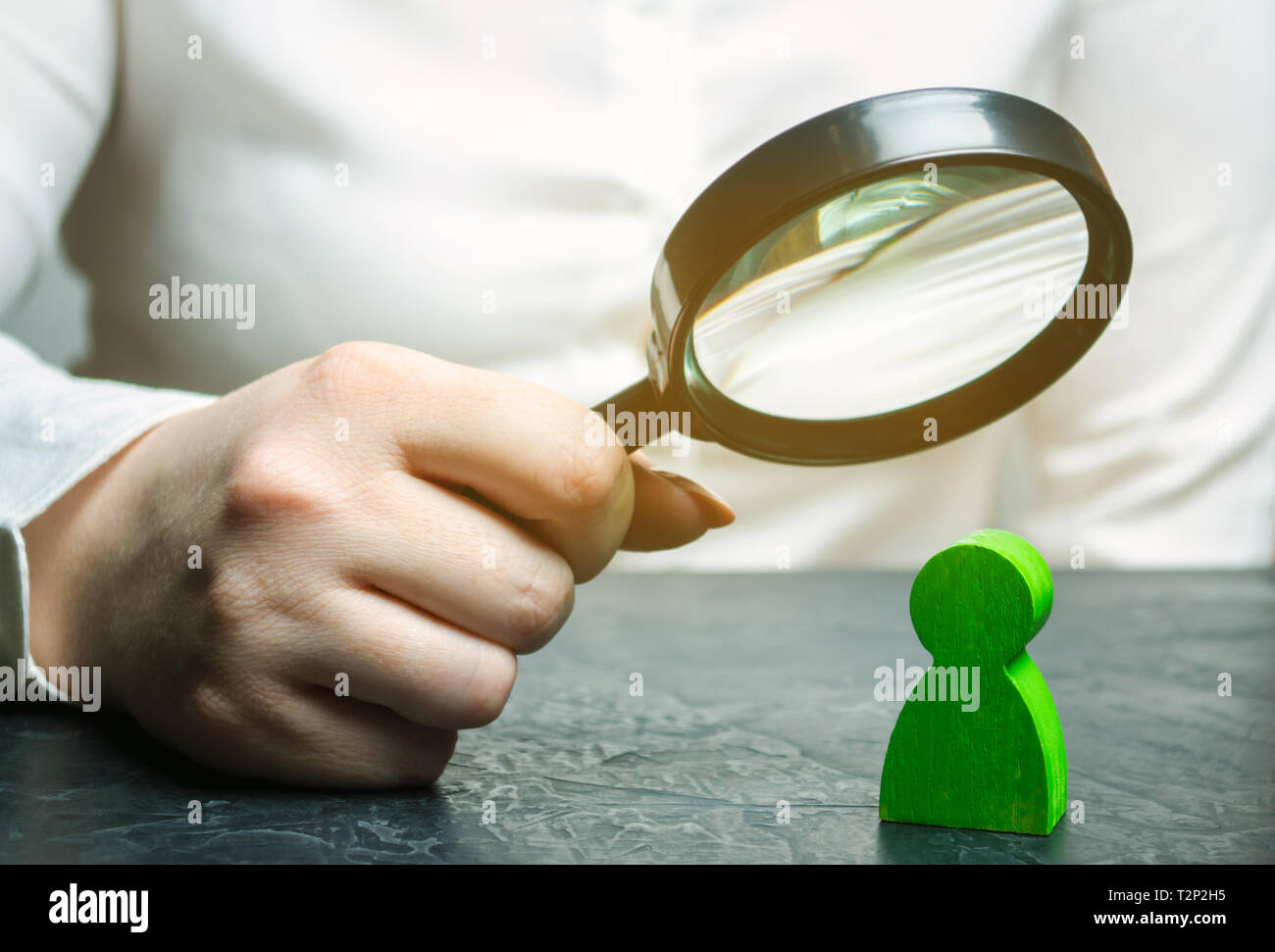 Businesswoman is holding a magnifying glass over a green man figure. Search for a talented employee. Identifying strengths in the company. Disclosure  - Stock Image