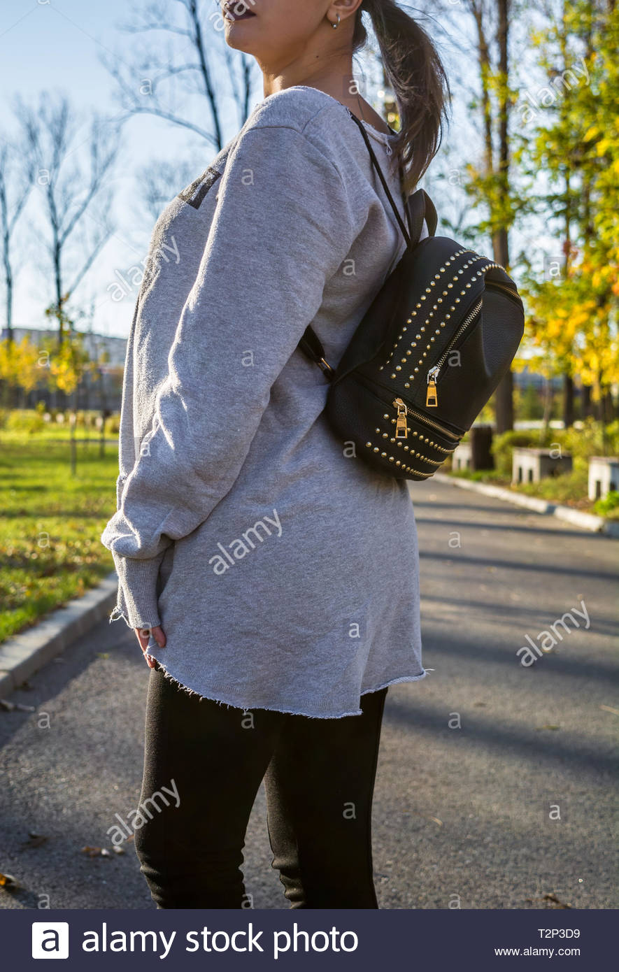 Woman in gray sweatshirt and black leggings wearing a leather backpack as accessory. Autumn and casual style. Blurred background. - Stock Image