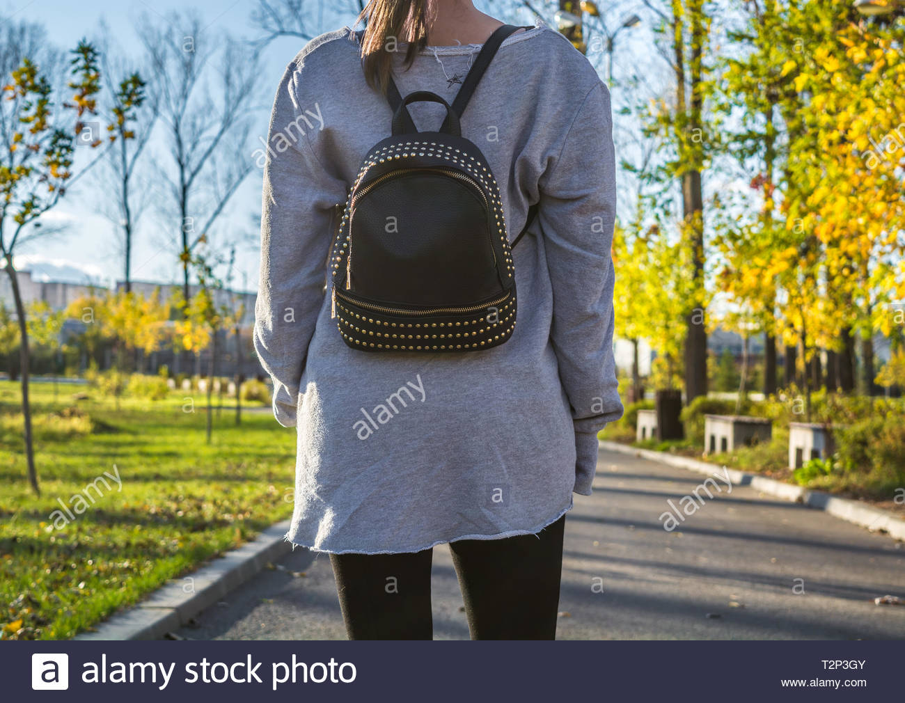 Young girl wearing gray sweatshirt and black yoga pants walking in the park. Black backpack with rhinestones as accessory. Casual style. - Stock Image
