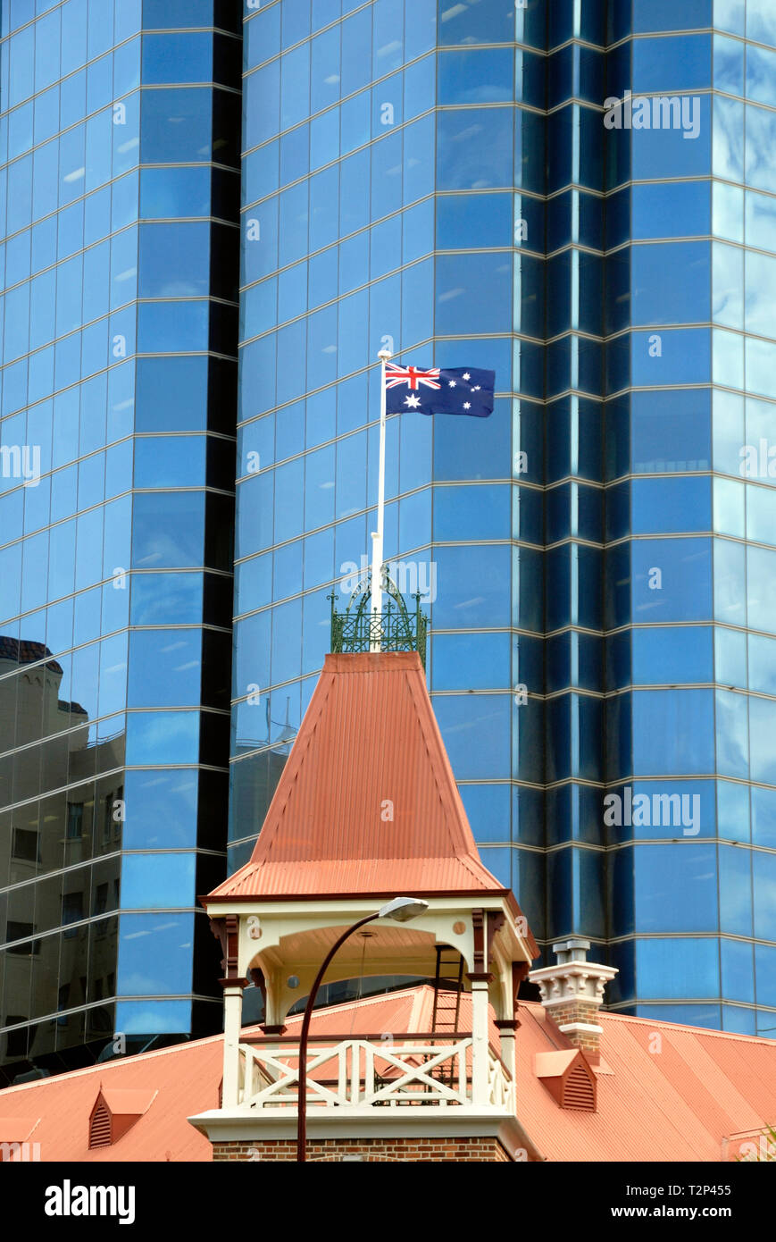 Australian flag flying on flagpole at the roof of an old fashioned building in front of an office building, Perth, Australia - Stock Image