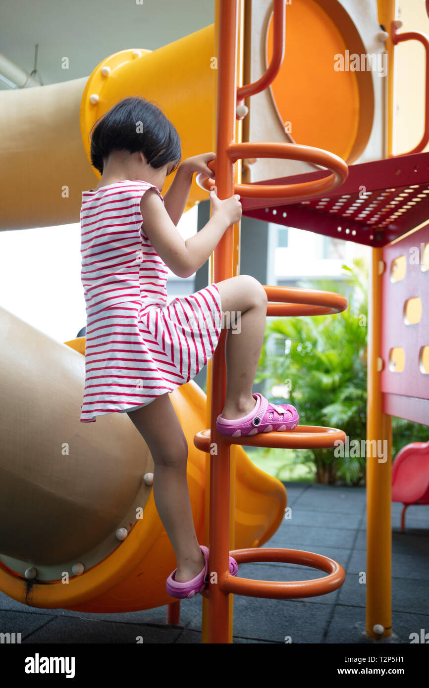Asian Chinese little girl climbing stepladder at outdoor playground Stock Photo