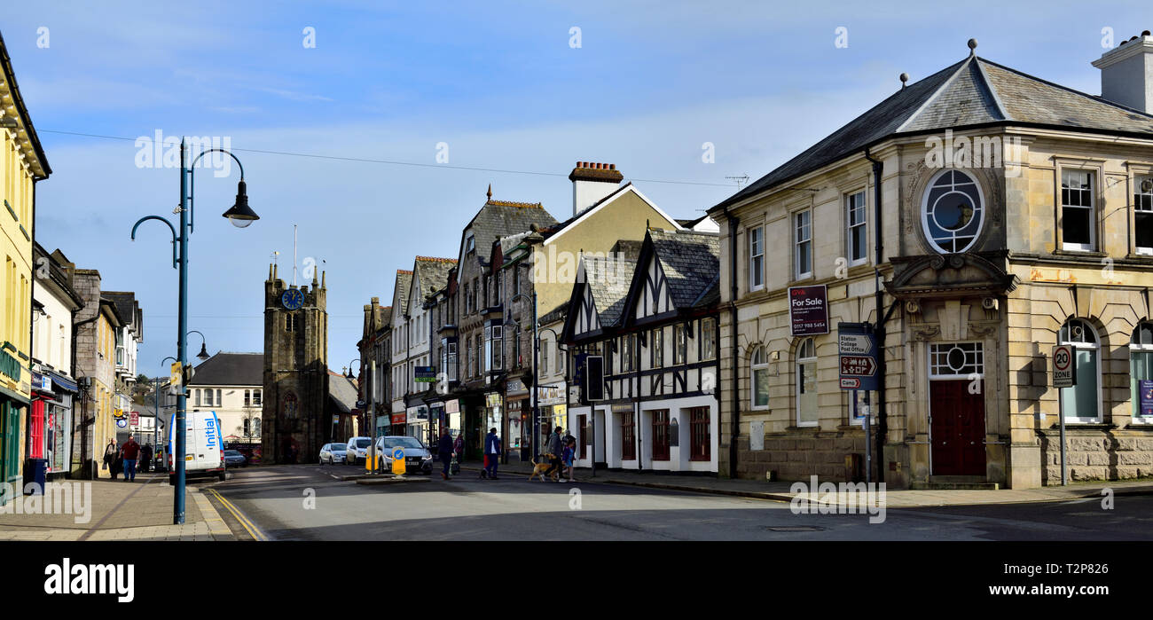 Looking down the main street, (Fore Street) in town of Okehampton with tower of St James Chapel at end, South Devon, England, UK - Stock Image