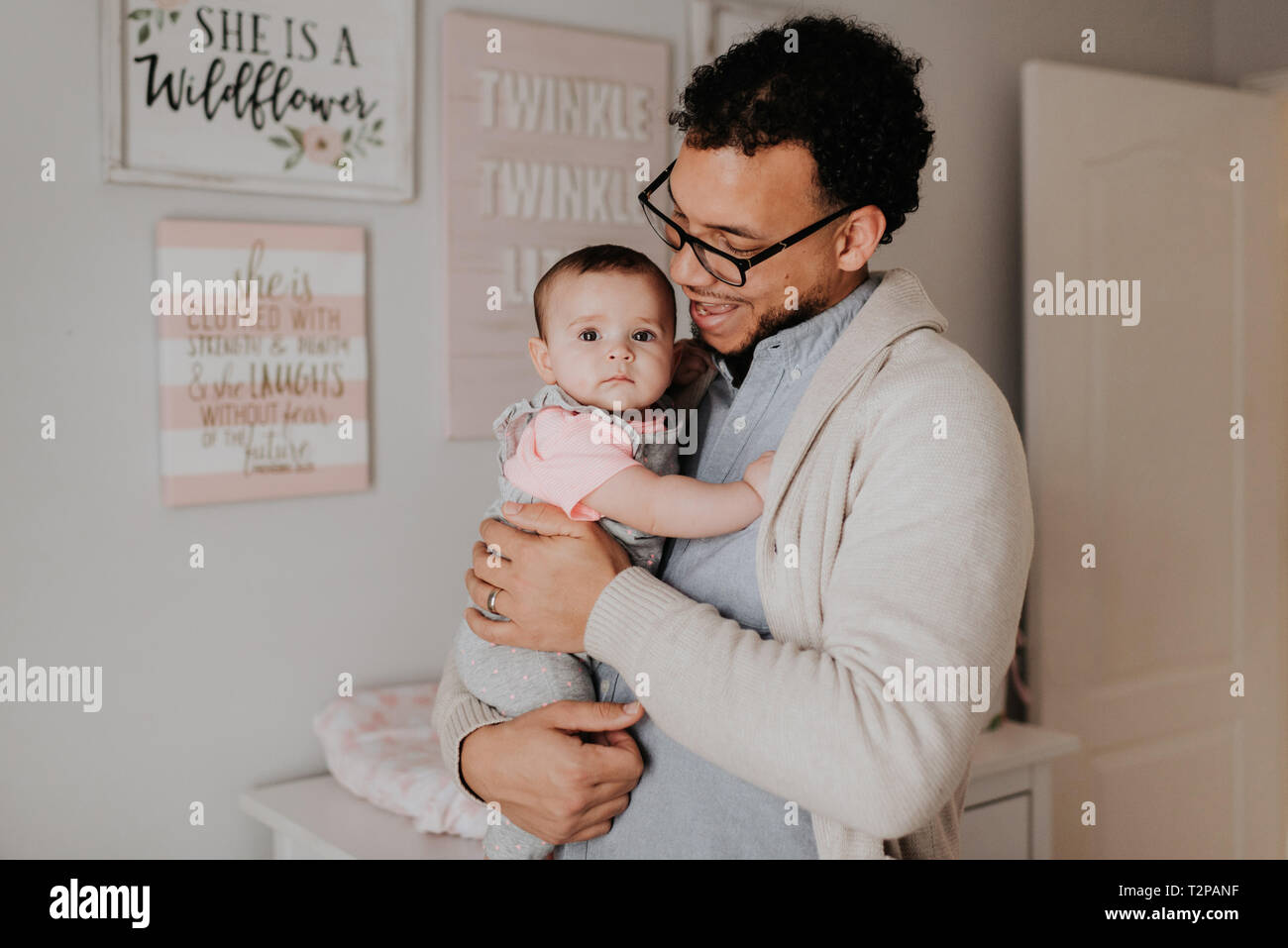 Father with baby daughter in baby's room - Stock Image
