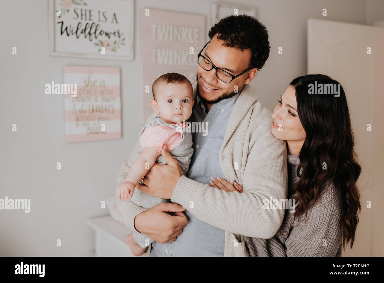 Couple with baby daughter in baby's room - Stock Image