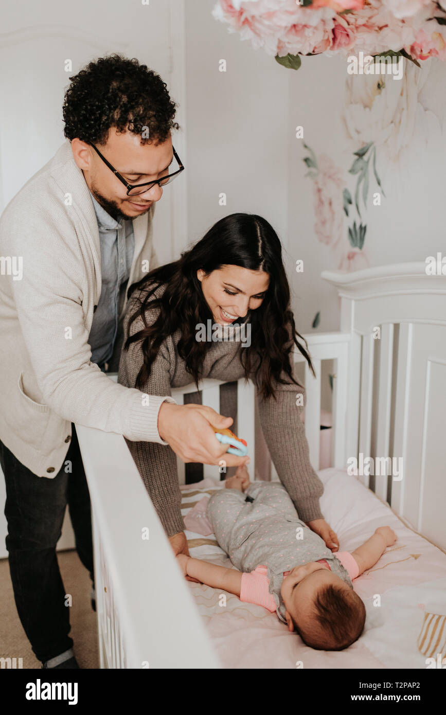 Couple putting baby daughter to bed in crib - Stock Image