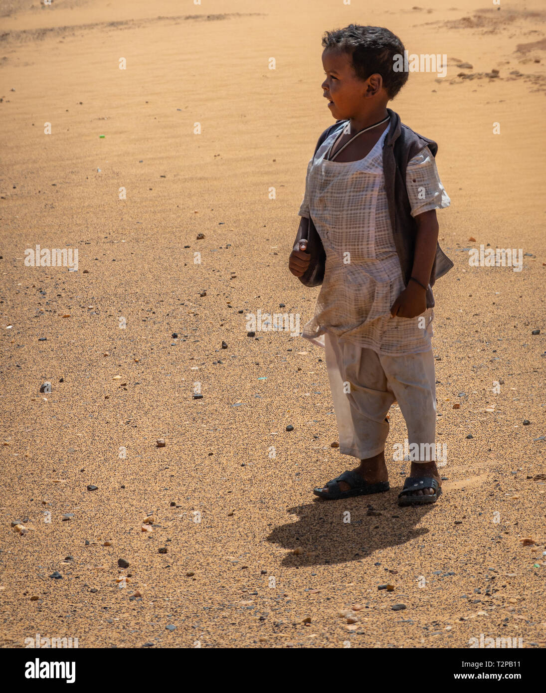 Kerma, Sudan, February 7., 2019: Small colored Sudanese boy with black hair, white pants, white shirt and dark blue vest looking sideways over the des - Stock Image