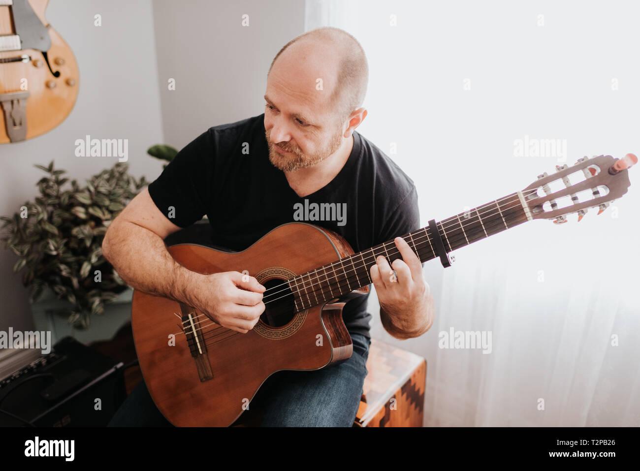 Man playing guitar at home - Stock Image