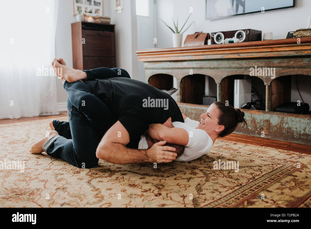 Couple wrestling on carpet at home - Stock Image