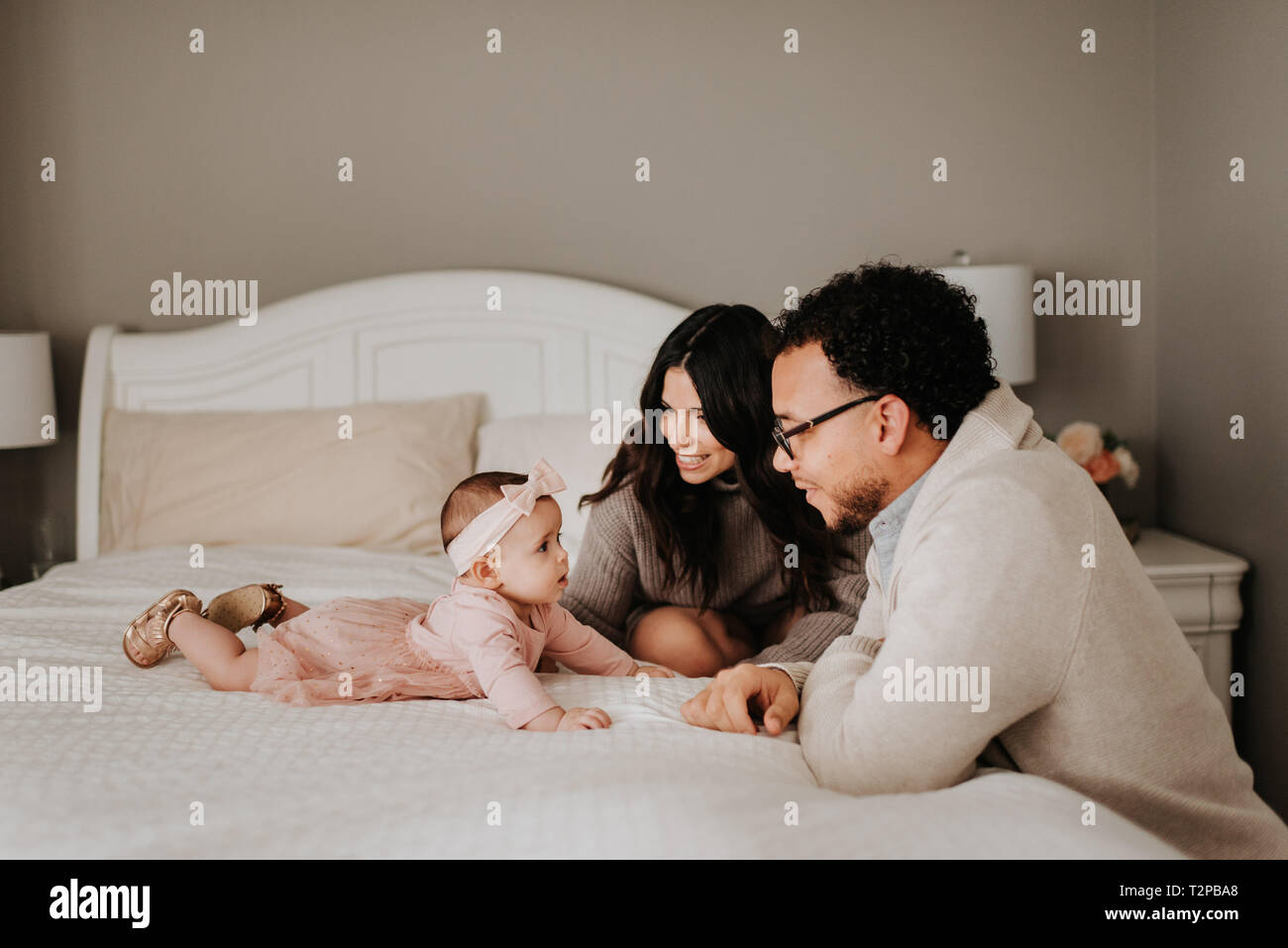 Couple with baby daughter on bed in bedroom - Stock Image