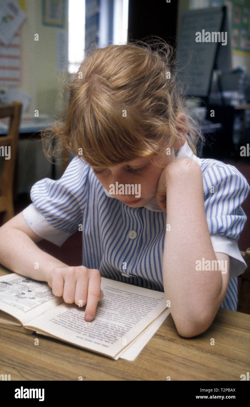 young girl reading in classroom Stock Photo