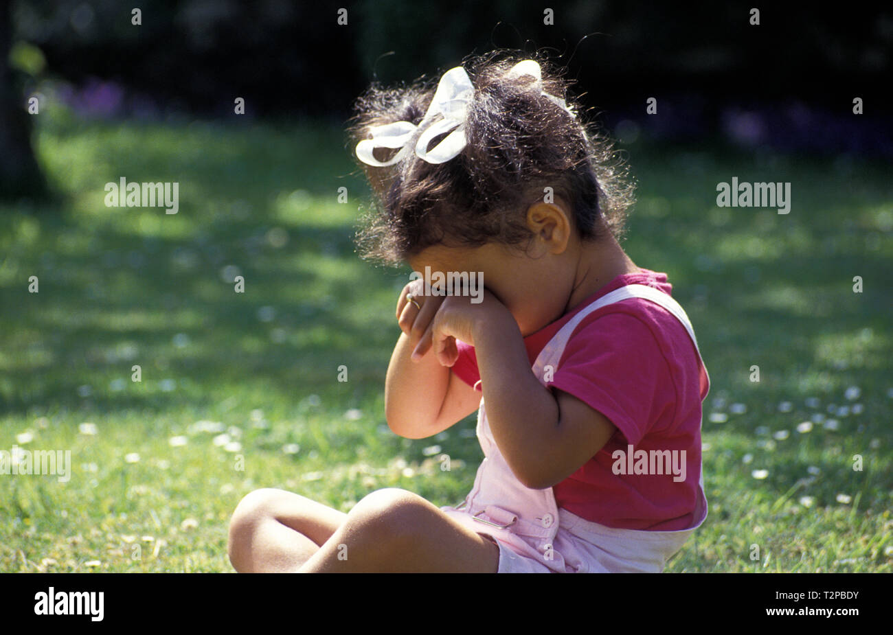 little girl sitting in garden rubbing her eyes - Stock Image
