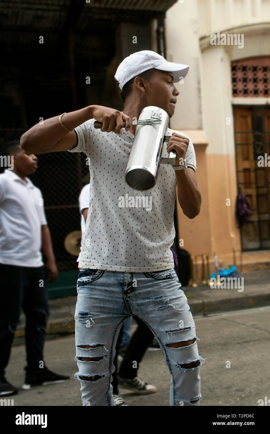 Young musician with his güira (metal scraper) during a percussion rehearse in downtown Panama City. Panama, Central America. Editorial use. Oct 2018 - Stock Image