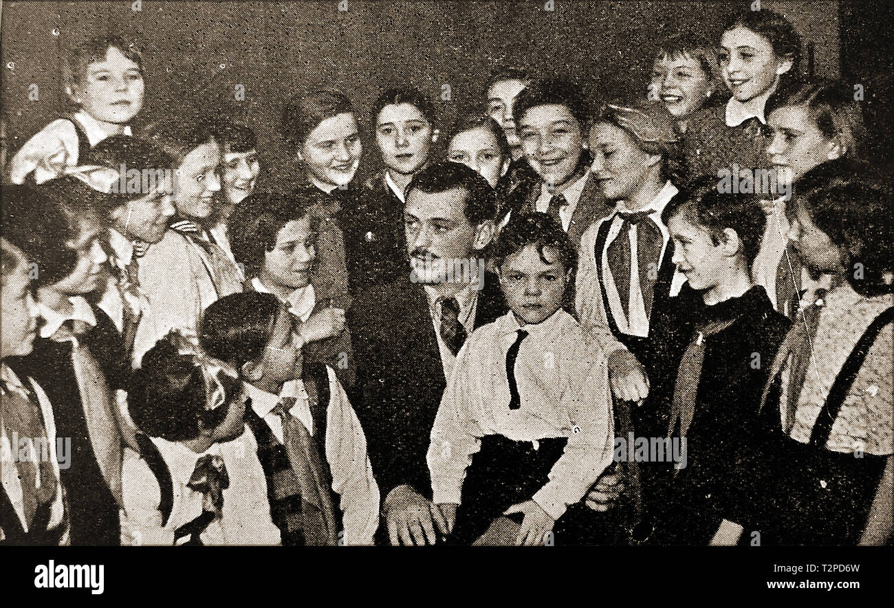 A 1940's portrait of Russian children's author M. Sergei Mikhalkov (aka  Sergey Vladimirovich Konchalovsky ) - 1913-2009 -with a group of Moscow,children. He composed the lyrics to the |Soviet National Anthem and wrote a number of satirical plays and comedy scripts and was awarded a number of  honours and awards - Stock Image