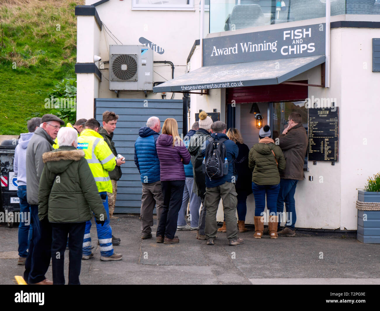 People queuing to buy award winning  Fish and Chips at the Seaview Cafe Restaurant on the sea front at Saltburn Stock Photo