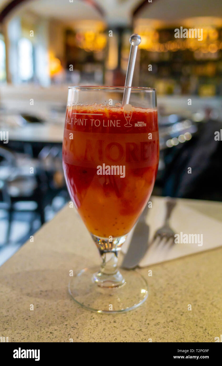 Refreshing fruit drink in an Italian Restaurant made from fresh oranges and raspberries. Stock Photo
