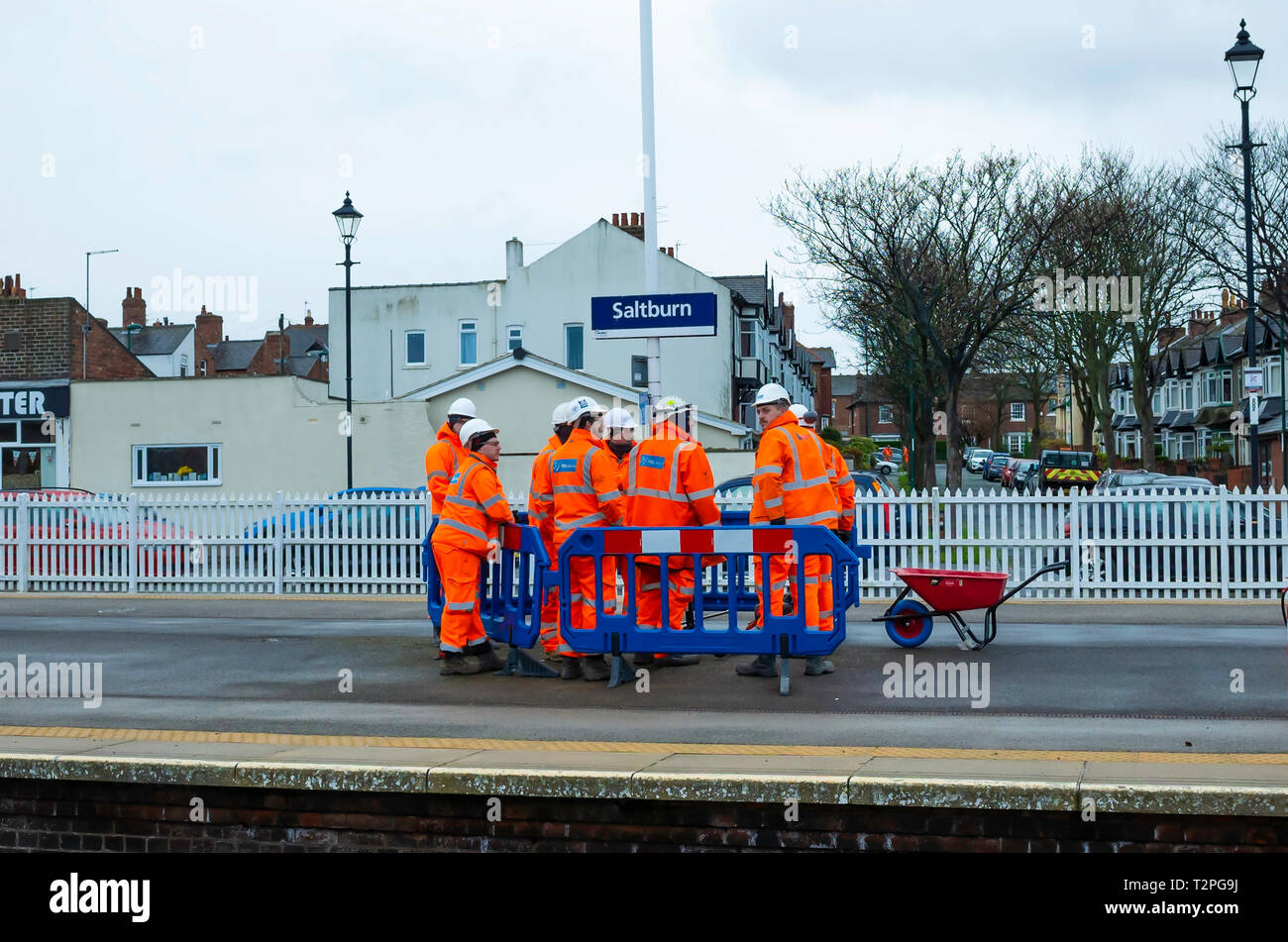 A gang of Railway Maintenance workers in orange overalls discussing a job on the Platform at Saltburn North Yorkshire Stock Photo