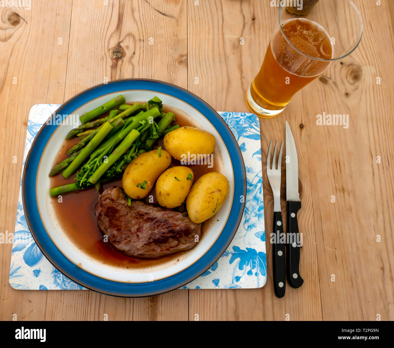 A fried Aberdeen Angus rump beef steak served with new potatoes, tenderloin broccoli and asparagus and gravy on a blue edged plate on a wooden table Stock Photo
