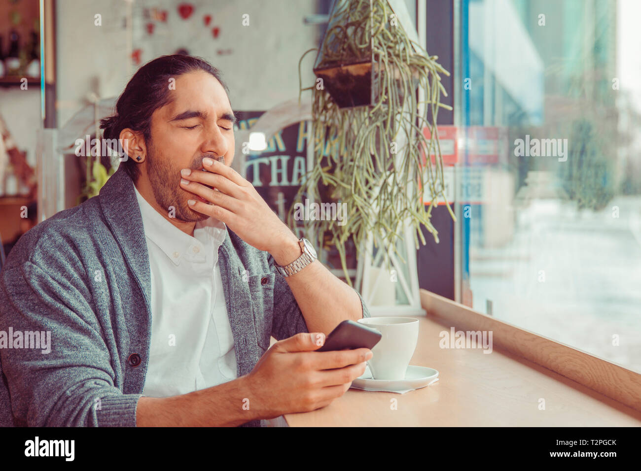 sleepy funny man, hand on mouth yawning looking at smart phone being bored by phone conversation, texting. Closeup portrait of a guy wearing casual we - Stock Image