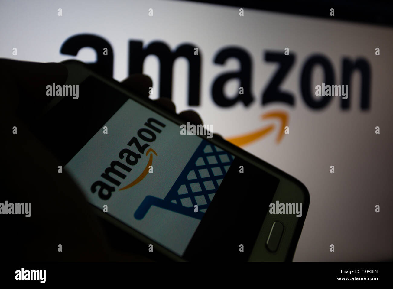 Amazon.com, American multinational technology company that focuses in e-commerce, logo is shown on a smartphone display, logo unfocused on background - Stock Image