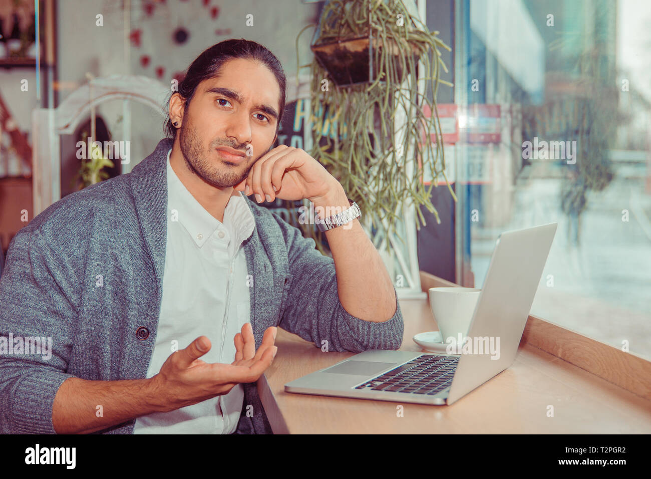 Man looking at you camera frustrated hand gesture in front of the computer. Closeup portrait of a handsome guy wearing white shirt, gray blouse sittin - Stock Image