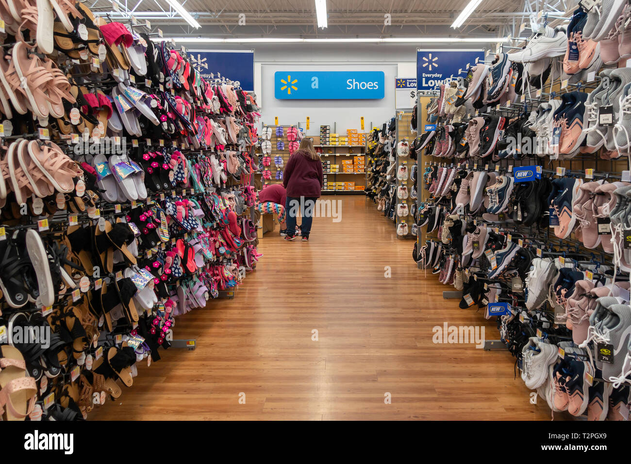 Walmart shoe department with two female customers trying on shoes. Wichita, Kansas, USA. Stock Photo