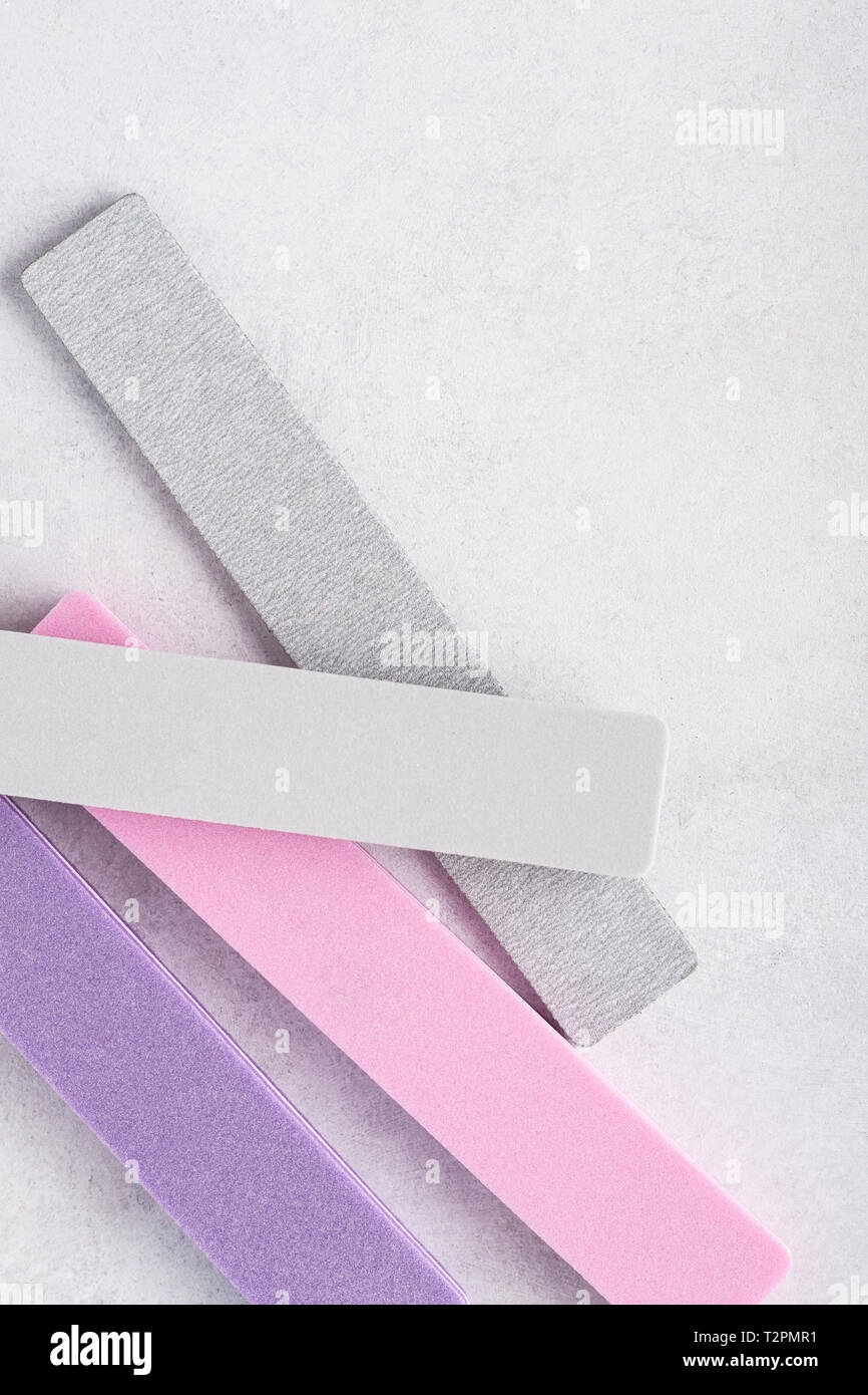 Colorful nail files on gray background. Manicure and pedicure tools. - Stock Image