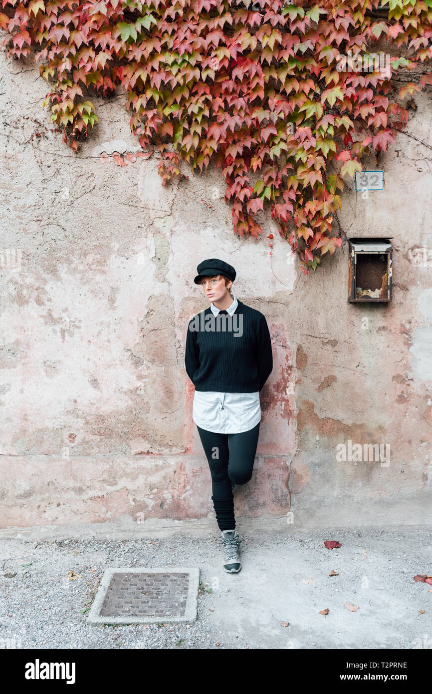Woman leaning against wall with ivy - Stock Image
