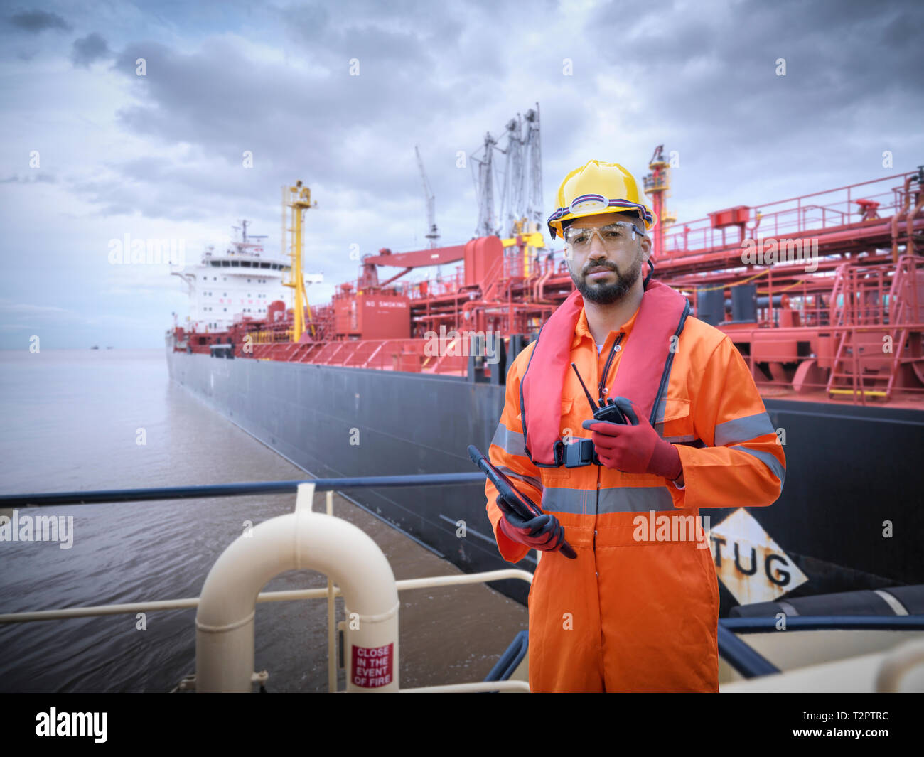 Composite image of ship worker on tugboat with oil tanker - Stock Image