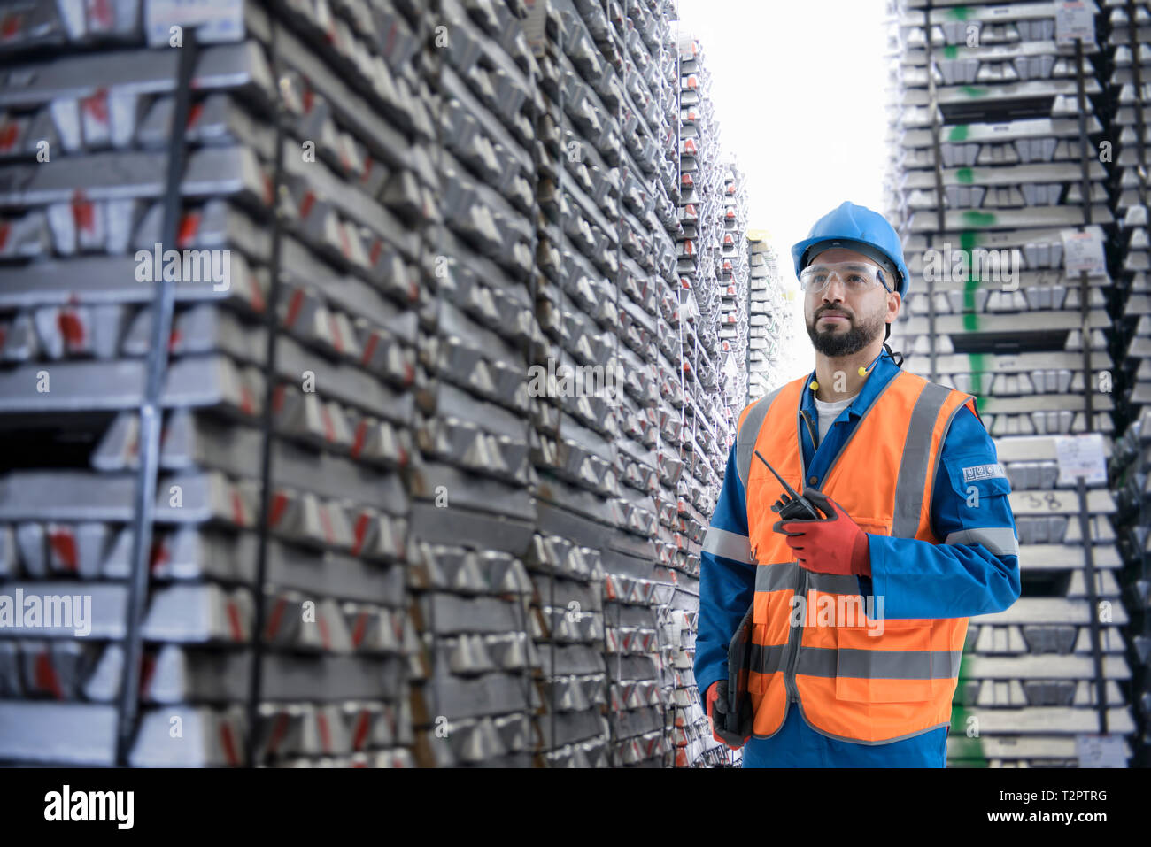 Composite image of worker with ingots of metal - Stock Image