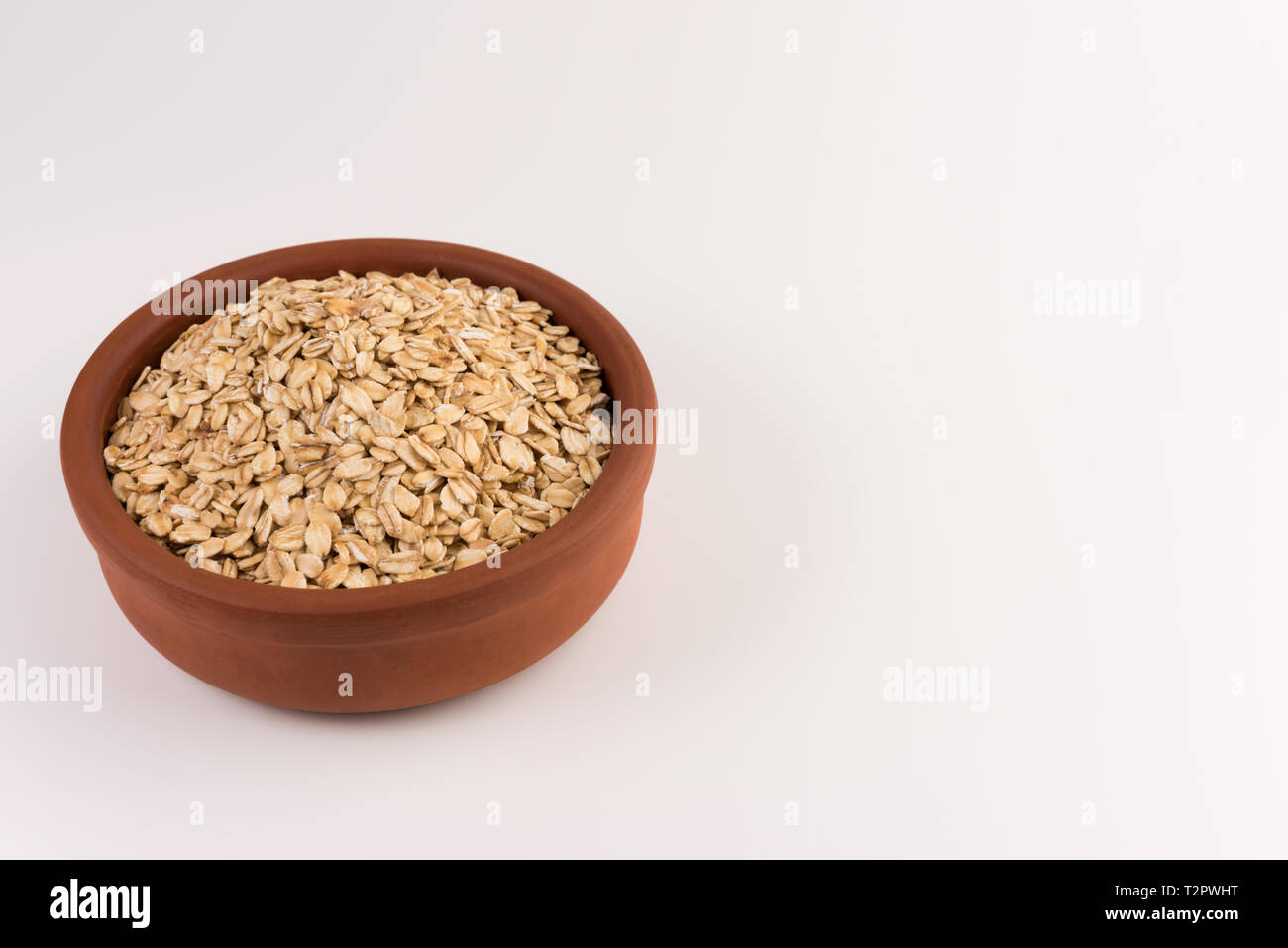 Dry rolled oatmeal in bowl isolated on white background. Stock Photo