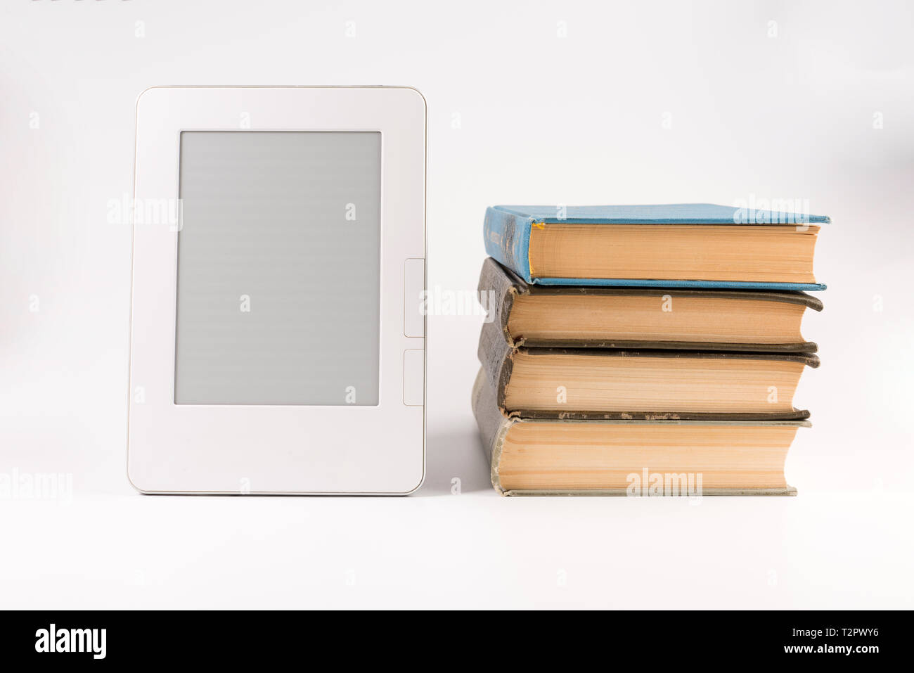 Electronic book with stack of regular old books isolated on white background - Stock Image