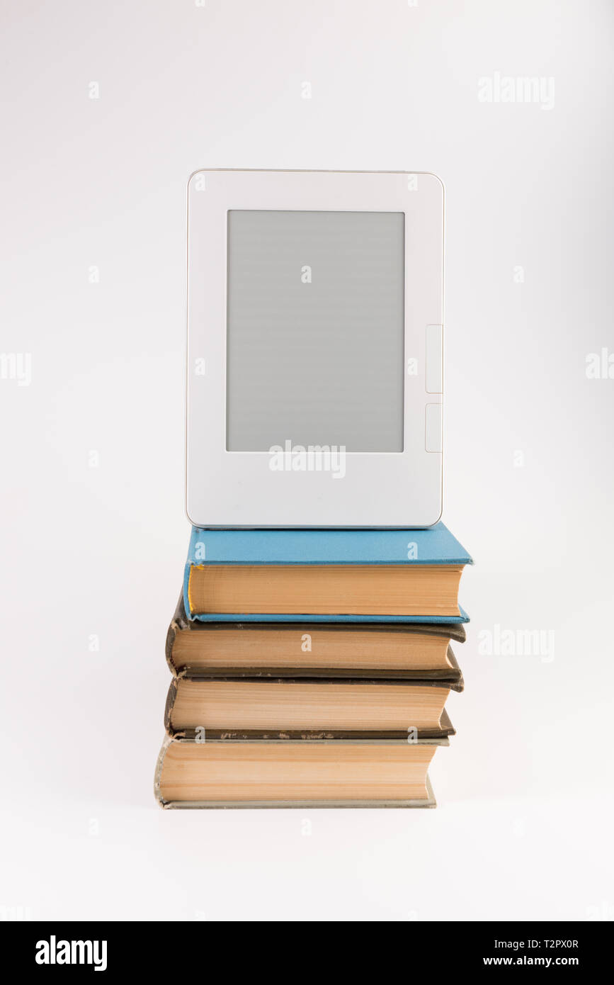 Electronic book on the top of the stack of regular old books isolated on white background - Stock Image