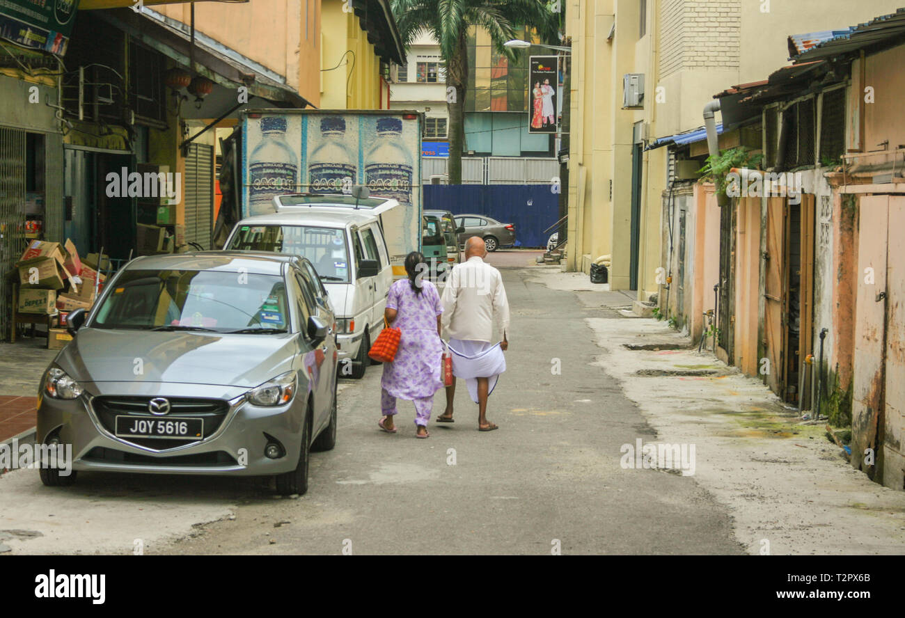 Local man and woman walking through the backstreets of the heritage district of Johor Bahru, Malaysia - Stock Image