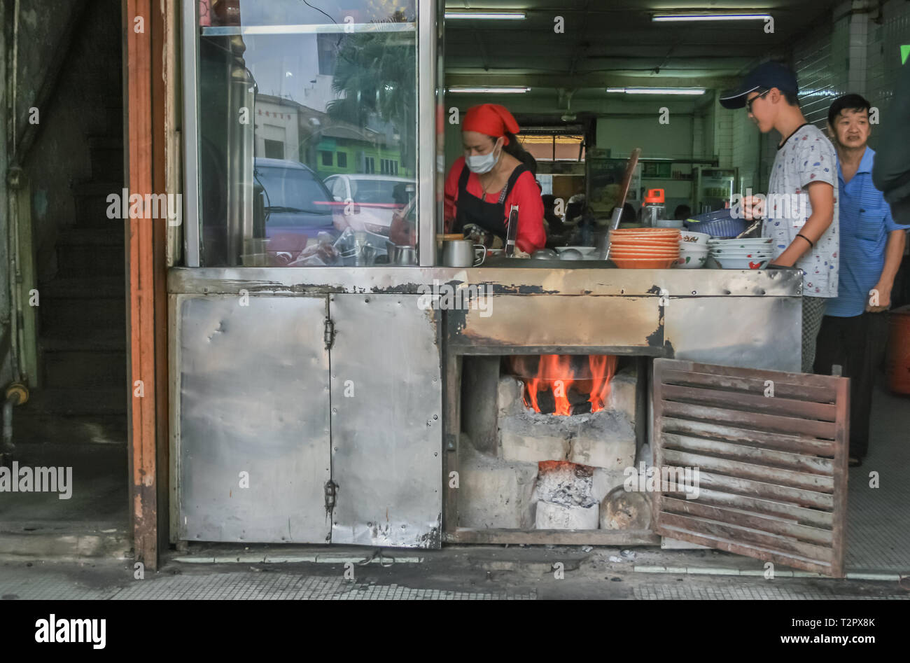 Lady cooking food in a traditional Chinese shophouse, Johor Bahru, Malaysia - Stock Image