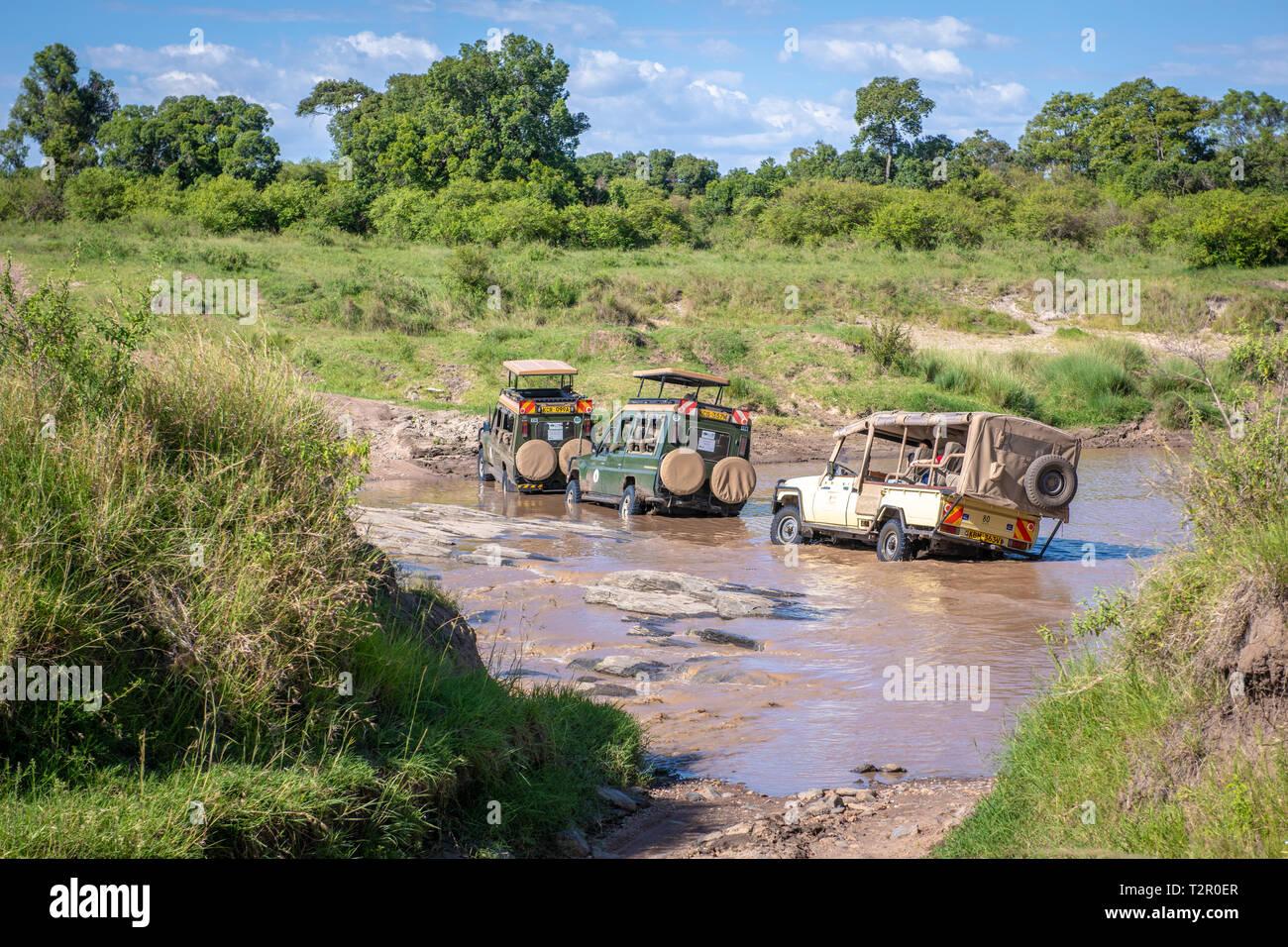 Game viewers carrying tourist drive through a stream in Maasai Mara National Reserve, Kenya - Stock Image