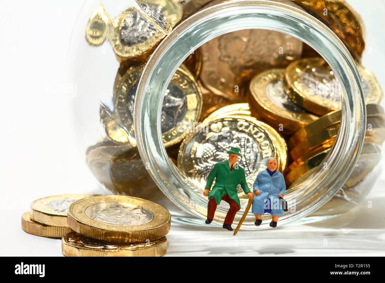 Conceptual diorama image of elderly miniature figures sat on the rim of a glass jar full of pound coins - Stock Image